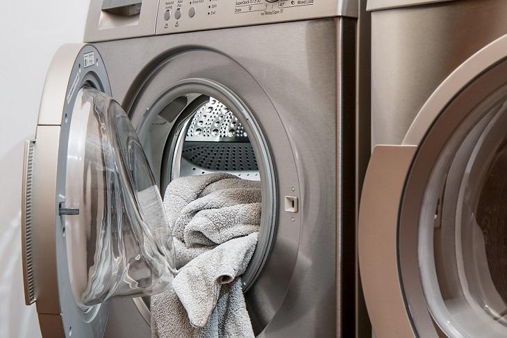 פריטים שאפשר להכניס למכונת כביסה: מכונת כביסה פתוחה שעל פתחה מונחת מגבת