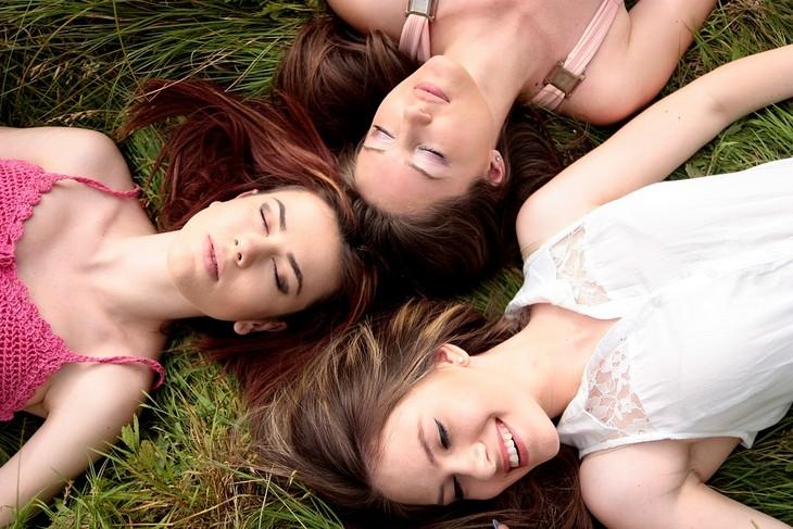 טיפים לשמירה על הביטחון העצמי: 3 בנות שוכבות על דשא כשראשיהן קרובים אחד לשני
