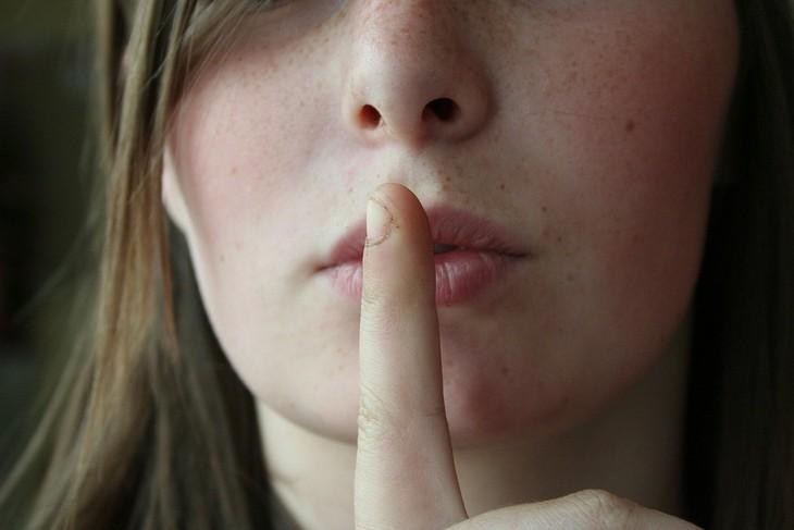 """טיפים לשמירה על הביטחון העצמי: אישה מסמנת """"שקט"""" עם אצבע"""