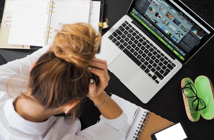 תלונות במערכות יחסים: אישה יושבת מול מחשב נייד ואוחזת בראשה