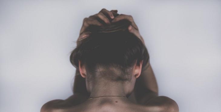 ערפול מוחי: אישה מצולמת מגבה ומחזיקה את ראשה בידיה