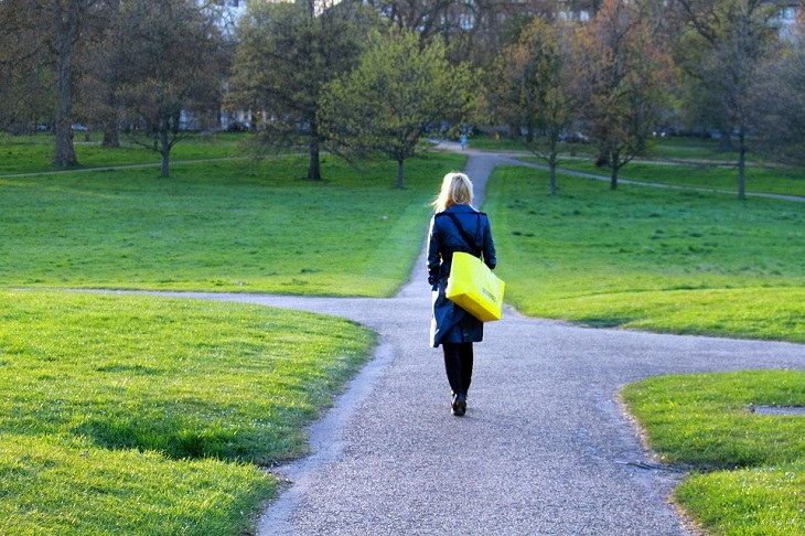 דרכים לשינוי תפיסה: אישה פוסעת לעבר התפצלות שבילים בפארק