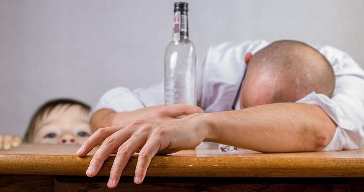 עצות להסברת נושא ההתמכרויות לילדים: אדם מעולף עם בקבוק משקה חריף בידו, וילד קטן מציץ עליו