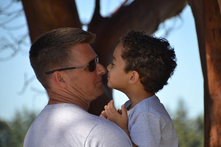 עצות להסברת נושא ההתמכרויות לילדים: אב מרים את בנו ומסתכל בעיניו