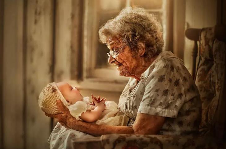 מצגת לסבא וסבתא: סבתא מחזיקה תינוק על הברכיים