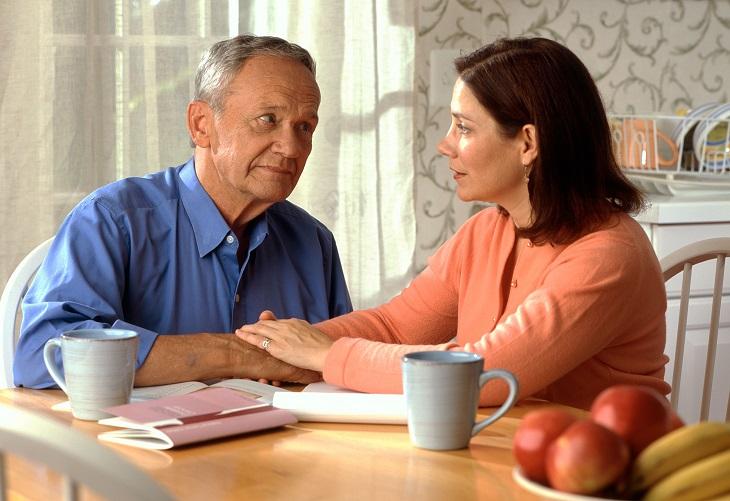 שינויים שזוגות צריכים לעשות: זוג בוגר יושב לצד שולחן, מביטים אחד על השני ואוחזים ידיים