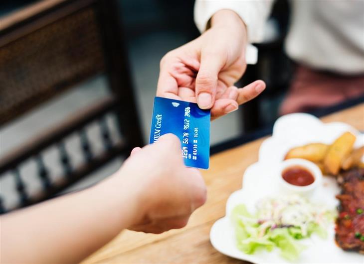מערכת נתוני אשראי: שני ידיים אוחזות בכרטיס אשראי משני קצוותיו