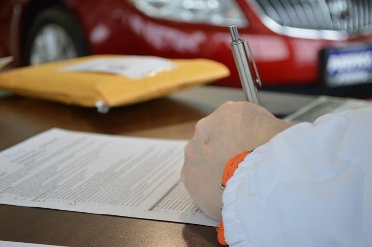 מערכת נתוני אשראי: איש אוחז בעט וחותם על מסמך