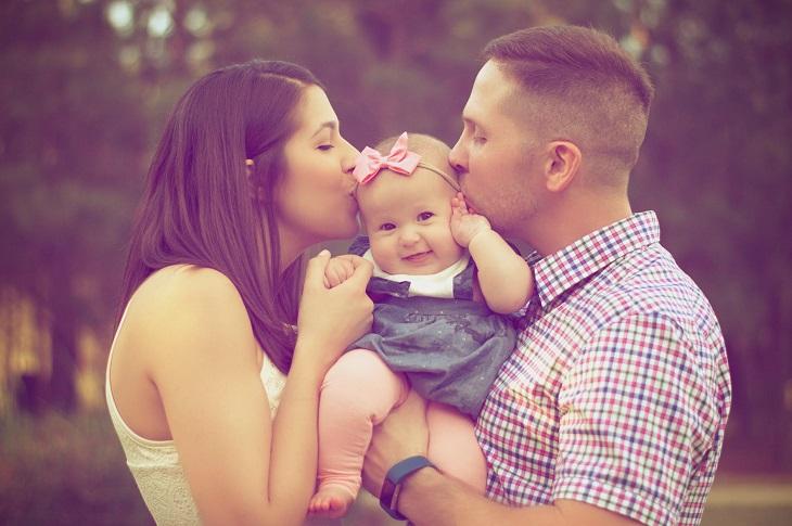 בעל תומך: הורים מנשקים תינוקת