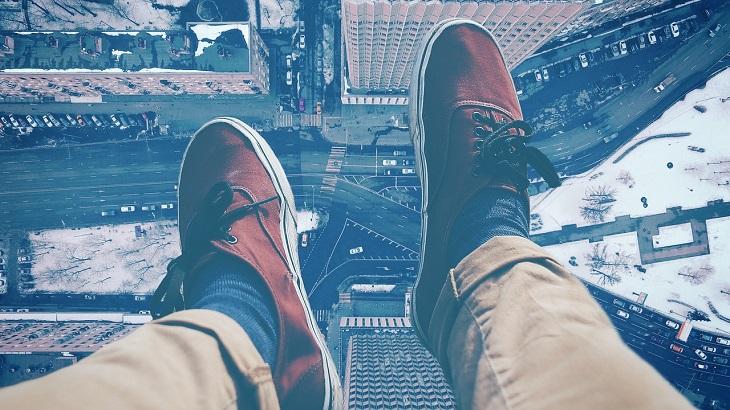 תכנות מחדש של התת מודע: רגלי אדם מתנופפות מגג בניין מעל עיר