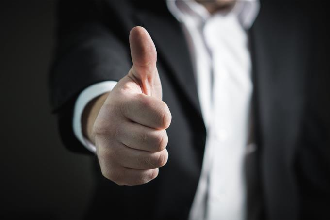 מבחן אישיות לשיפור החיים: סימן אגודל למעלה של גבר בחליפה
