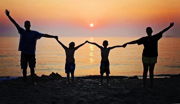 השפעות של פעילות גופנית: משפחה מאושרת על חוף הים