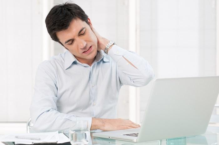 6 תרגילים לשחרור צוואר כואב ותפוס: אדם עובד מול מחשב ונוגע בעורף תפוס