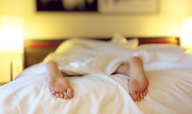 תרגילי מתיחות לשינה טובה: כפות רגליים של אדם ששוכב על הבטן במיטה
