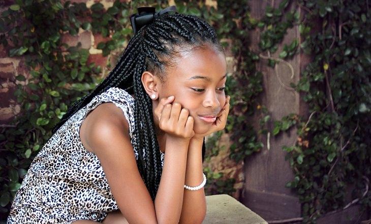 ילדה משעינה את ראשה על כפות ידיה