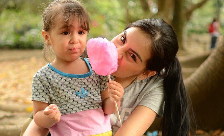 כיצד למנוע השמנת יתר אצל ילדים: ילדה אוחזת במקל שיערות סבתא, ואמה אוכלת ממנו