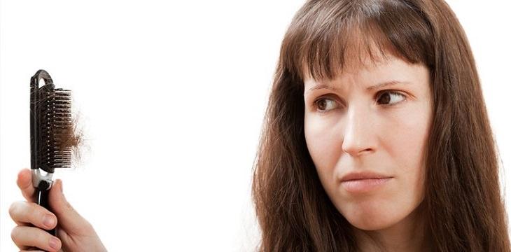סיבות לנשירת שיער: אישה ומברשת שיער מלאה שיערות