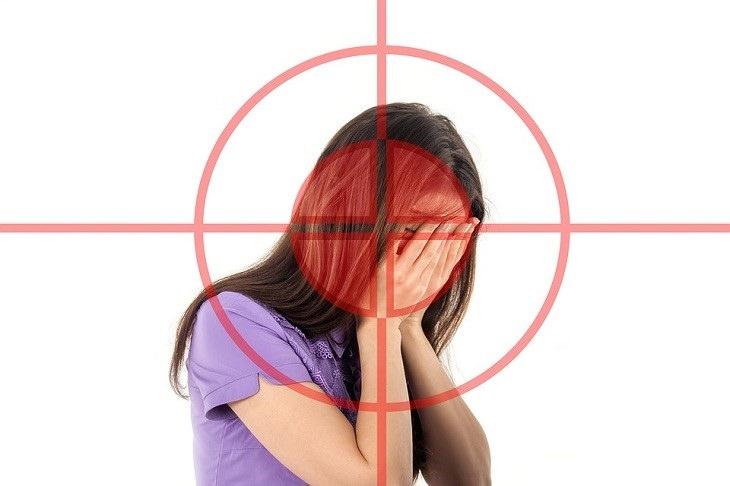 סיבות לכאבי ראש: איור של כוונת על אישה שמחזיקה את ראשה
