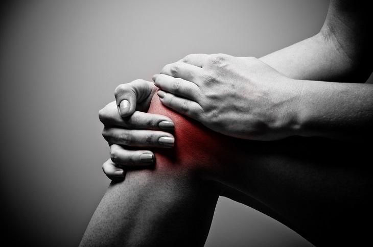 תרגילים לכאבי ברכיים: גבר מחזיק את ברך ימין