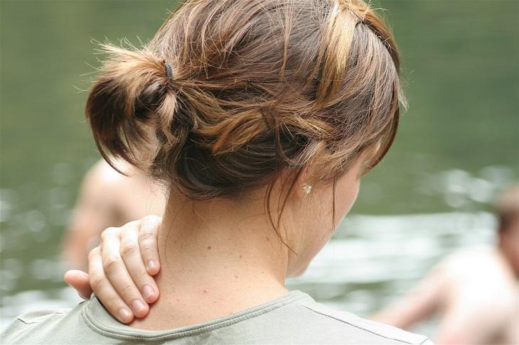 תרגיל פשוט לטיפול בצוואר תפוס: אישה אוחזת לעצמה בעורף