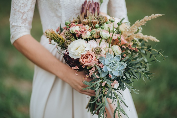 עיצוב חתונת וינטאג': אישה בשמלת כלה מחזיקה זר פרחים