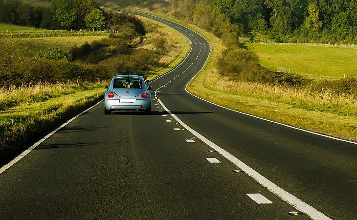 למה לקנות מכונית חדשה: מכונית נוסעת על כביש ליד שדה ירוק