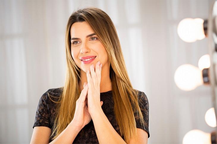 יתרונות הטיפוח של הקולגן: אישה מביטה במראה