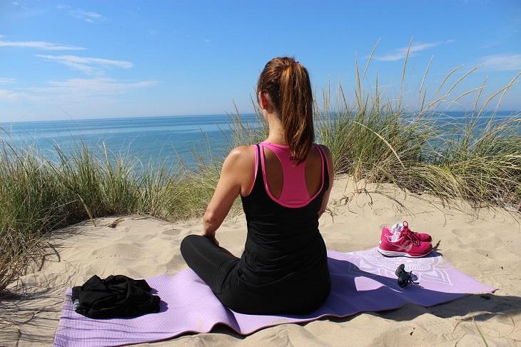 תרגילי יוגה לשיפור חילוף החומרים: אישה מתרגלת יוגה על החוף
