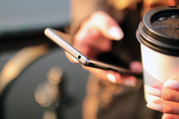 אפליקציות תשלום לנסיעות באוטובוסים: בחורה מחזיקה סמארטפון וכוס קפה