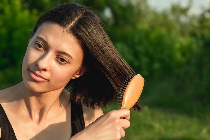 טעויות בסירוק שיער: אישה מברישה את קצוות השיער