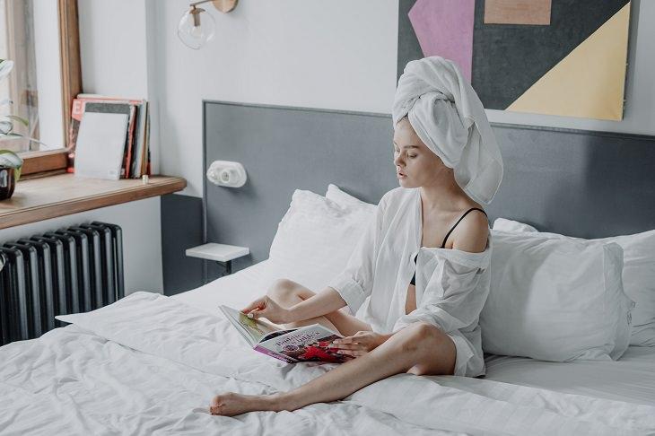 טעויות בסירוק שיער: אישה יושבת על מיטה, כשמגבת עוטפת את שיערה