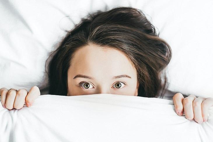 שיטת שינה: אישה מכסה את הפנים עם שמיכה