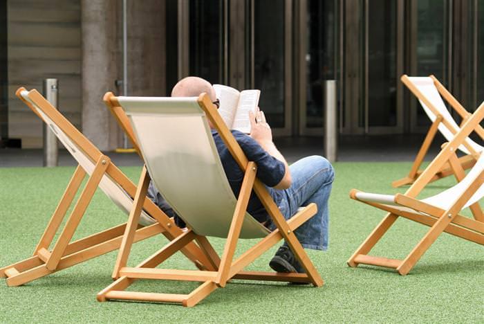 יתרונות של קריאת ספרים: גבר מבוגר יושב על כיסא בחוץ וקורא ספר