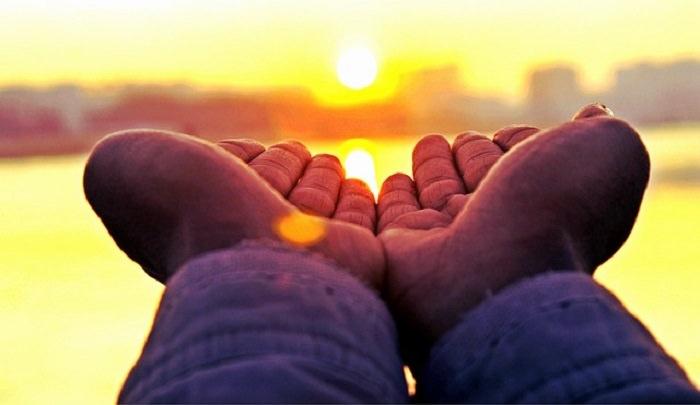 ברכה מרגשת: כפות ידיים של אדם על רקע השקיעה