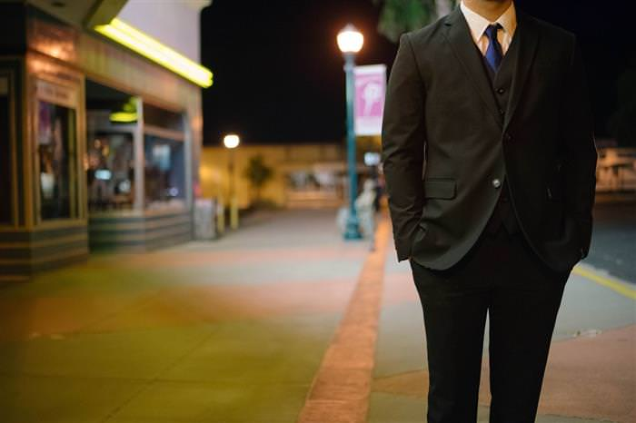 טיפים לחיזוק האסרטיביות והביטחון העצמי: גבר עם חליפה הולך ברחוב