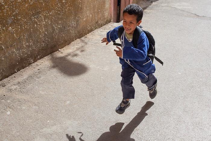 יתרונות ארוחת הבוקר: ילד מחויך רץ עם ילקוט על גבו