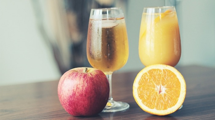 מאכלים בריאים שגורמים לאי נעימות: כוס סיידר תפוחים שלצדה תפוח אדום, וכוס מיץ תפוסים שלפניה חצי תפוז
