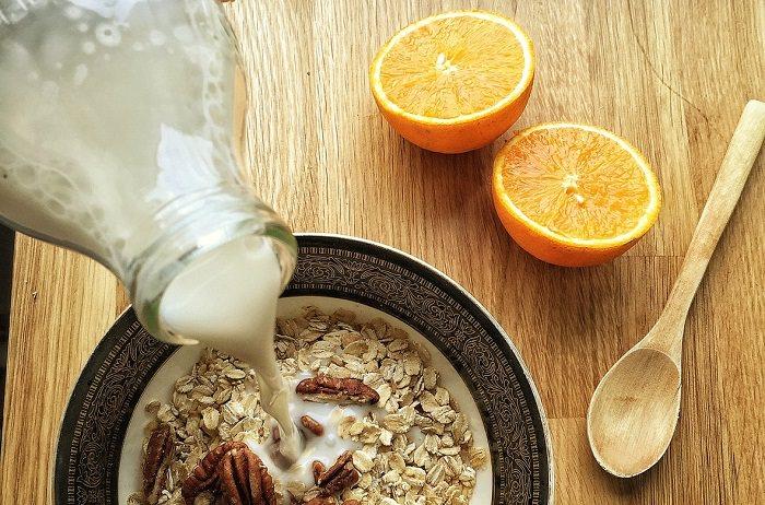 מאכלים בריאים שגורמים לאי נעימות: קערת שיבולת שועל בחלב שאליה נמזג עוד חלב, ולצידה כף מעץ ותפוז חצוי