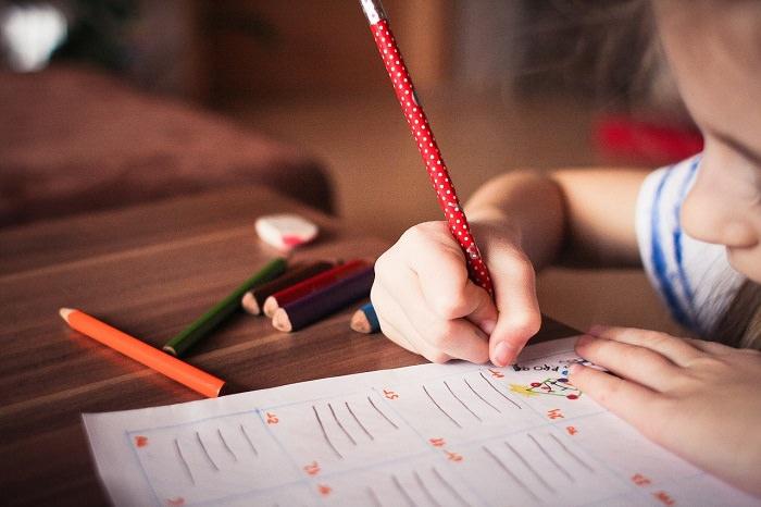 איך ללמוד נכון: ילדה קטנה מציירת על חוברת עבודה