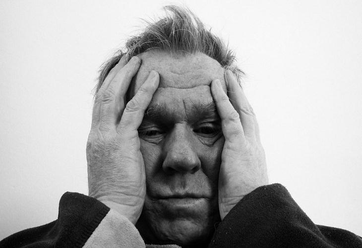 איש מבוגר מחיזק את ראשו בתסכול