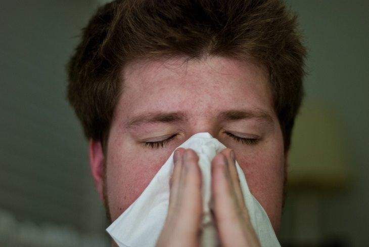איש מקנח את האף