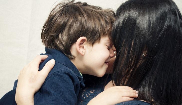 איך להפסיק אלימות מילולית בקרב ילדים: אימא מחבקת את הילד שלה