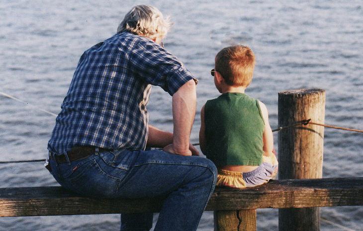 ילד ואיש מבוגר יושבים ליד הים