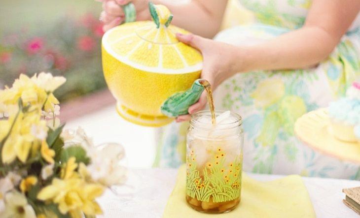 לימונדת כורכום: יד מחזיקה קנקן עם ציור של לימון ומוזגת לימונדה לכוס