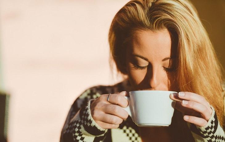 לימונדת כורכום: אישה מחזיקה ספל ולוגמת משקה