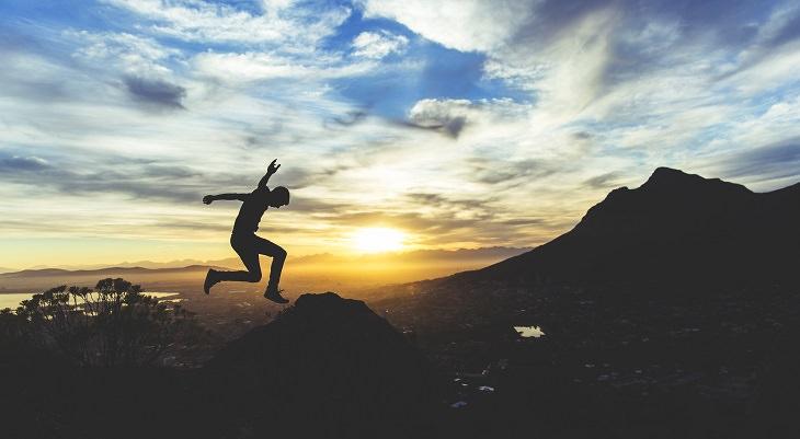 אדם צעיר קופץ באושר וברקע נוף הרים
