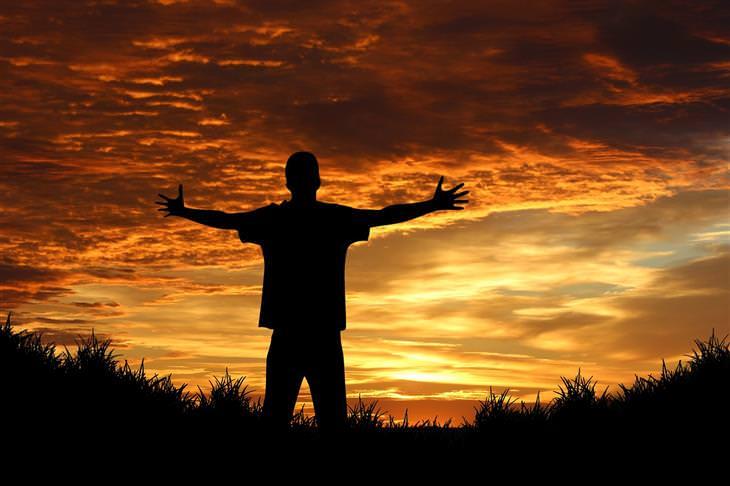 צללית של איש עומד מול השקיעה עם ידיים פרושות לצדדים
