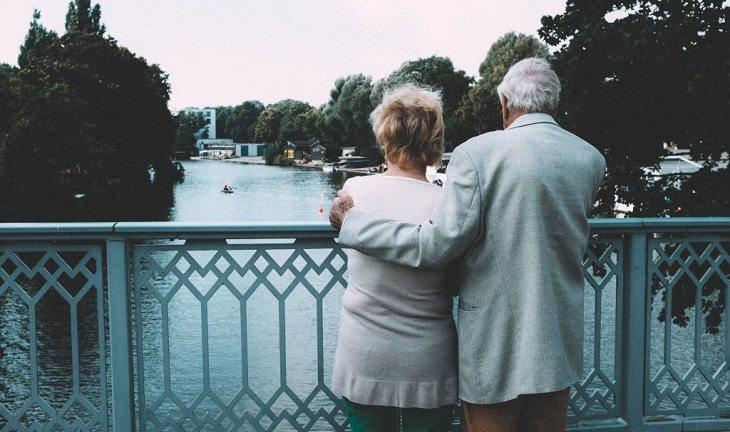 זוג מבוגר עומד על מעקה של גשר וצופה לאופק