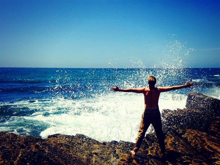 איש עומד מול הים עם ידיים פרושות לצדדים