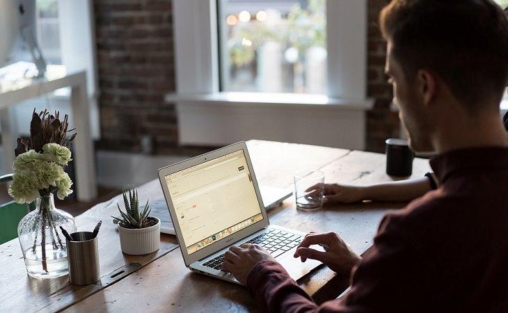 תרגילי כושר משרדיים: אדם יושב מול שולחן משרדי עם מחשב נייד